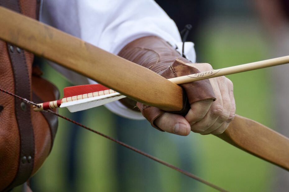 Types of bows. Longbow and arrow being nocked.