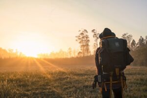 What should I take in a survival kit? Backpacker walking at dawn.