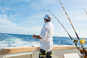 Fishing boat safety. Man saltwater fishing in boat.