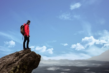 Best Apps for Camping And Hiking. Man on mountain top hiking.