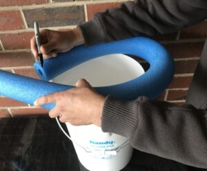 DIY toilet bucket. Marking the pool noodle with a Sharpie.