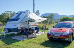 Motor home and travel trailer accessories. Couple enjoying camping with travel trailer.
