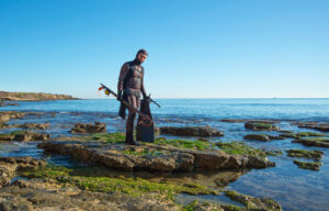 Male with wetsuit and spearfishing gear on rocks.