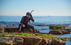 Wetsuits for spearfishing. Male getting ready to spearfish.