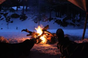 Winter camping tips. Campfire in snow.