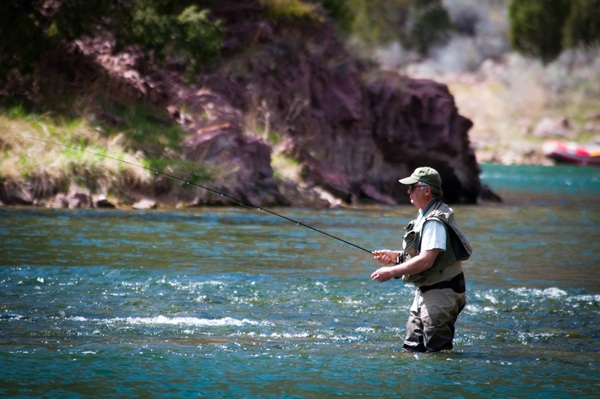 What is a tippet in fly fishing? Male fly fishing in river.